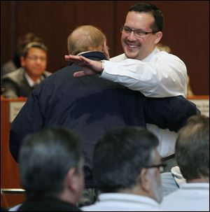 Shaun Enright is embraced by  George Tucker, exec. secretary-treasurer of the Toledo area AFL-CIO Council, after being appointed as the new member of Toledo City Council during a vote at Council Chambers at Government Center.