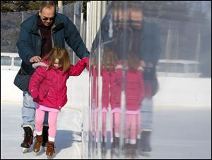 Chuck McKeown of Toledo helps steady his granddaughter, Addison McKeown, 5, as she takes to the ice for the first time at the Ottawa Park skating rink Monday.