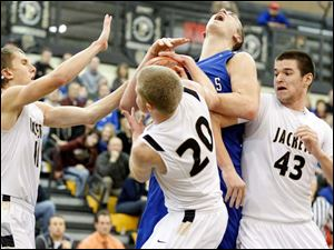 Anthony Wayne's Mark Donnal (34) battles Perrysburg's Matt Kaczinski (20) and Nate Patterson (43) for a rebound during Tuesday's game. At left is Perrysurg's  Bryant Byrd (11).