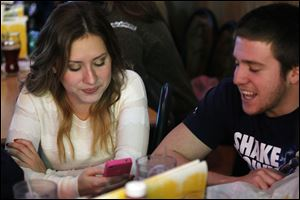 Ashley Langsdorf, 18, and a friend, Anthony Russo, 18, a freshman at Bowling Green State University, keep an eye on her Twitter feed during a party for her mother, Josie.