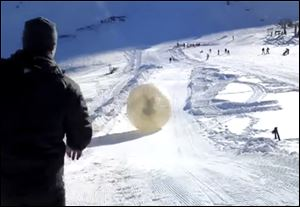 Denis Burakov and another man are seen inside a large plastic ball called a zorb last Thursday as they roll down a hill beore tragedy struck at the winter sports venue at Dombai in the Caucasus Mountains of southern Russia.  What was supposed to be a thrilling ride down a ski slope inside a giant inflatable ball has ended in tragedy when the zorb veered off course and sailed over a cliff, killing Denis Burakov and leaving the other man badly injured.
