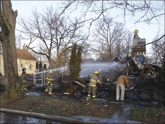CTY fire10p fernwood fire Toledo firefighters pour water on a house as Toledo city workers demolish it on Fernwood Avenue.