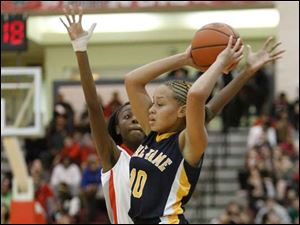 Notre Dame Academy player Destinee Battle looks to pass the ball as Central Catholic High School's Kiana McClendon, 12, defends.