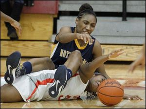Notre Dame Academy player Kaayla McIntyre lands on Central Catholic High School player Sydni Harmon as they battle for a loose ball.