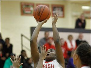 Central Catholic High School player Sydni Harmon shoots over Notre Dame Academy player Faith Mitchell.
