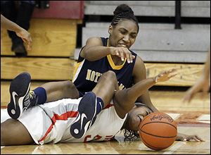 Notre Dame's Kaayla McIntyre lands on Central Catholic's Sydni Harmon as they scramble for a loose ball during the third quarter Thursday night.