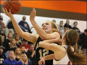Perrysburg's senior guard Maddie Williams (12) pushes past Southview's sophomore Maria Pappas (12) as she goes in for a layup.