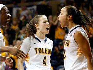 University of Toledo's Inma Zanoguera, right, (23) cheers with her teammates Naama Shafir (4) and after sinking a layup and being fouled during the second half of Thursday evening's home game against Central Michigan University.
