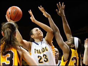 University of Toledo's forward Inma Zanoguera (23) attempts to put up two points from the lane under pressure from Central Michigan University defenders during the second half of Thursday evening's home game.