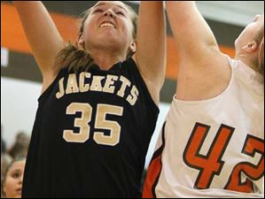 Perrysburg's sophomore center Allex Brown (35) puts up two points under pressure from Southview's sophomore Emily Westphal (42).