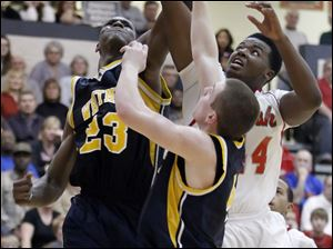 Whitmer's Nigel Hayes (23) goes to the net against Central Catholic's Keith Towbridge (44).