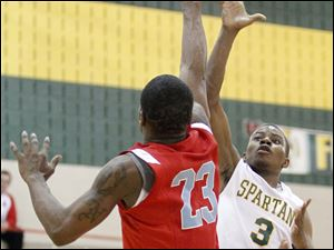 Start High School player Dion Ivery, 3, shoots over Bowsher High School player Nate Allen, 23.