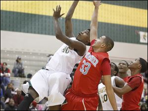 Start High School player Michael Mitchell, 40, puts up a shot against Bowsher High School player Marcus McGovern, 33.