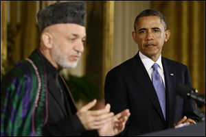 President Barack Obama listens as Afghan President Hamid Karzai speaks during their joint news conference in the East Room at the White House in Washington.