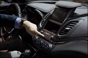 A representative from General Motors opens a compartment inside a Chevy Impala while demonstrating the MyLink connection and entertainment system.