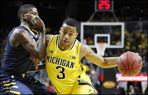 Michigan sophomore Trey Burke drives against West Virginia's Eron Harris. Burke, a Columbus native who won Mr. Basketball in Ohio, leads the Wolverines with an 18.2 scoring average.
