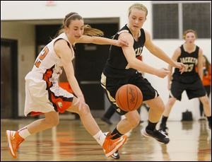 Southview's sophomore Maria Pappas (12) retains control of the ball after an attemptedd steal by Perrysburg's senior guard Maddie Williams (12) during the quarter of Friday night's game at Southview. The Yellow Jackets beat the Cougars 53-39.