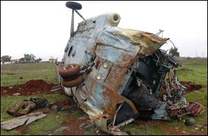 This citizen journalism image provided by Edlib News Network, ENN, which has been authenticated based on its contents and other AP reporting, shows a dead Syrian soldier, left, loyal to Syrian president Bashar Assad, on the ground next to a destroyed helicopter at Taftanaz air base.