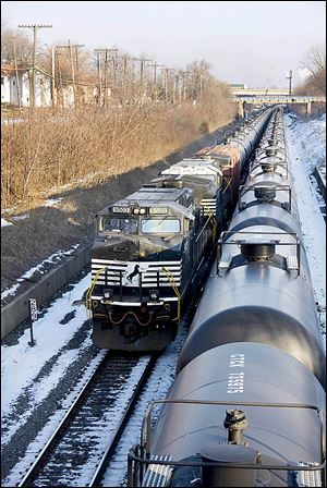 A Norfolk Southern train hauls empty oil tank cars in Toledo. Experts say rail travel is riskier than pipelines, but is faster to start up.