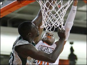 Bowling Green State University player Richaun Holmes, 22, has his dunk attempt blocked by Eastern Michigan University player Glenn Bryant, 23, during the first half at Bowling Green State University.
