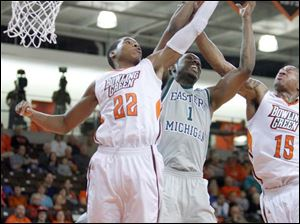 Bowling Green State University players Richaun Holmes, 22, and A'uston Calhoun, 15, battle for a rebound with Eastern Michigan University player DaShonte Riley, 1, during the first half at Bowling Green State University.