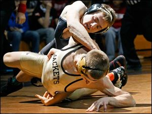 Delta's Tyler Fahrer attempts to pin Perrysburg's Ryan Roth during the championship match in the 145 pound weight class of this year's Perrysburg Invitational Tournament Saturday at Perrysburg High School.  Roth won, 5-3.