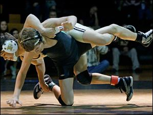 Perrysburg's Mario Guillen struggles to keep Delta's Jake Spiess down during the championship match in the 113 pound weight class of this year's Perrysburg Invitational Tournament Saturday at Perrysburg High School. Guillen won, 12-8.