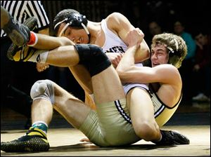 Perrysburg's Rocco Caywood, right, grapples with Fostoria's Tony Reynolds during the championship match in the 170 pound weight class of this year's Perrysburg Invitational Tournament Saturday at Perrysburg High School. Caywood won, 2-1.