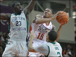 Bowling Green State University player A'uston Calhoun, 15, shoots against Eastern Michigan University defenders Glenn Bryant, 23, and J.R. Sims, 2, during the second half at Bowling Green State University.