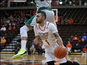 Bowling Green State University player Jordan Crawford, 1, fakes Eastern Michigan University player Jamell Harris, 32, off of his feet during the first half.