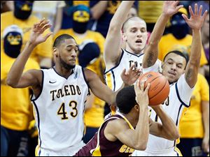 University of Toledo defenders Matt Smith (43), Richard Wonnell (55) , and Josh Lemons (11) put pressure on Central Michigan guard Chris Fowler (15).