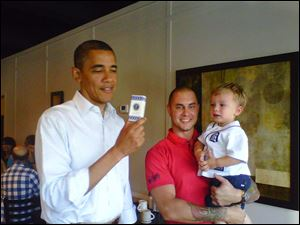Brian Malkowski holds his son Liam Ryan as they meet President Obama at Rick's Diner.