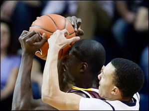 University of Toledo guard Josh Lemons (11)  battles Central Michigan forward Oliver Mbaigoto (25) for the ball.