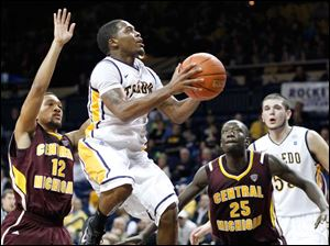 University of Toledo guard Julius Brown (20) goes to the net  against  Central Michigan's Kyle Randall (12) and Olivier Mbaigoto (25.