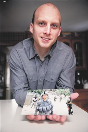 Kyle Tucker, of Sylvania, poses with a picture of himself during his 2008 deployment to Afghanistan.
