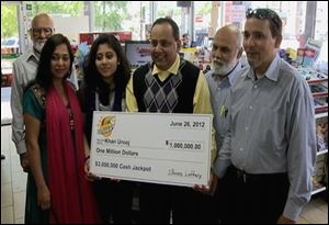 Urooj Khan, center, holding a ceremonial check in Chicago for $1 million as winner of an Illinois instant lottery game. At left, is Khan's wife, Shabana Ansari. Khan, 46.