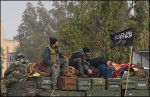 Rebels from al-Qaida affiliated Jabhat al-Nusra sit on a truck full of ammunition, at Taftanaz air base.