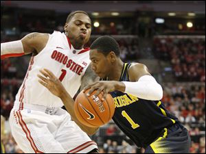 Ohio State's DeShaun Thomas, left, tries to slow down Michigan's Glenn Robinson III, right, during the second half of an NCAA college basketball game toady in Columbus. Ohio State won 56-53.