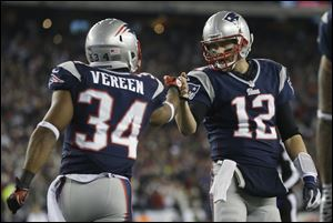 New England Patriots running back Shane Vereen, left, is congratulated by quarterback Tom Brady after Vareen's eight-yard touchdown reception Sunday in Foxborough, Mass. Brady got his 17th playoff win, the most for any quarterback, in New England's 41-28 AFC divisional victory over Houston on Sunday.