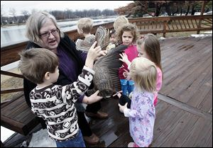 Maureen Schnell of Eco-Discovery shows youngsters a wing from a Canada Goose during the Nurturing Nature program at Olander Park in Sylvania on Friday.  Jamie Valasek, 3, left, holds a model of an owl while Jackie Jennewine, 2, right, touches the wing.  Nature topics vary week to week.
