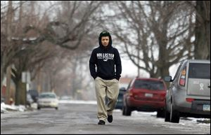 Ramon Allen, 15, walks down Prouty Avenue on his way home from school. He blames the violence on 'gang wars' and fights that start in public and end in neighborhood shootings.