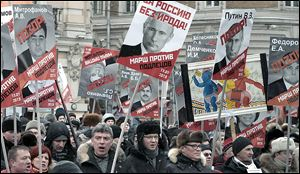 People carry posters of Russian President Vladimir Putin  during a protest in Moscow against Parliament's ban on U.S. adoptions. Many ques­tioned the moral prin­ci­ples of a ban in a nation with so many chil­dren in fos­ter care or or­phan­ages.