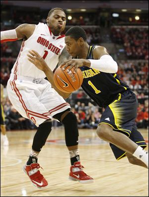 Ohio State's DeShaun Thomas drives past Michigan's Trey Burke in the first half. Thomas scored 20 to lead the No. 15 Buckeyes.