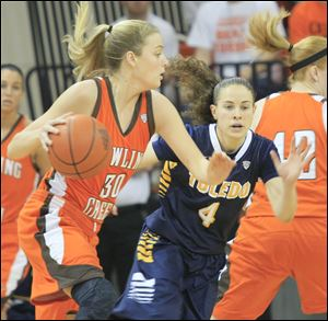 BGSU's Miriam Justinger, left, dribbles past UT's Naama Shafir in the first half Sunday in Bowling Green. Toledo won 48-38.