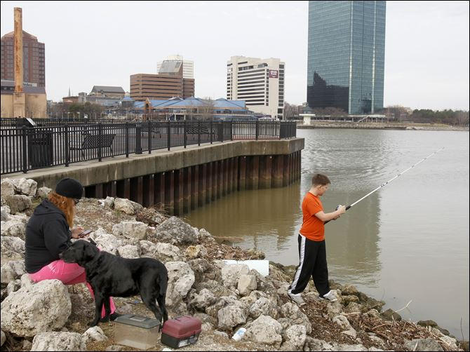 Nancy Thomas of Toledo, with her dog Jade, son Tyler Thomas Nancy Thomas of Toledo, with her dog Jade, joins her son Tyler Thomas, 12, as he puts his Christmas-gift fishing rod to the test at International Park across from downtown.