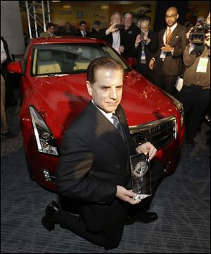 Cadillac Chief Engineer David Leone kneels in front of the Cadillac ATS which was named North American Car of the Year.