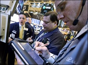 Traders work on the floor of the New York Stock Exchange. Stocks opened lower on Wall Street as concerns about the government's finances intensified, offsetting a report that showed retail sales rose in December.