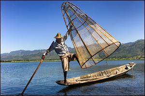 A fisherman does a balancing act with his boat, net, and oar in Inle Lake, Myanmar.