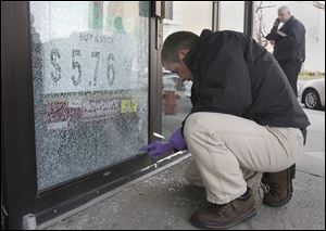 TPD's Terry Cousino digs for the bullet that lodged into the door at the Madison Market/Le Pam Pam store in Toledo.