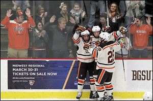Bowling Green's Robert Shea, right, celebrates with his teammates during the Falcons' win against Notre Dame on Tuesday night at BGSU Ice Arena.